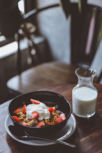 photo bowl of cereal with strawberries beside glass of milk on table free for commercial use images