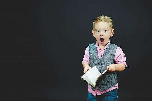 photo boy wearing gray vest and pink dress shirt holding book free for commercial use images