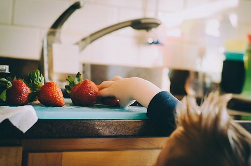 child picking strawberries in kitchen