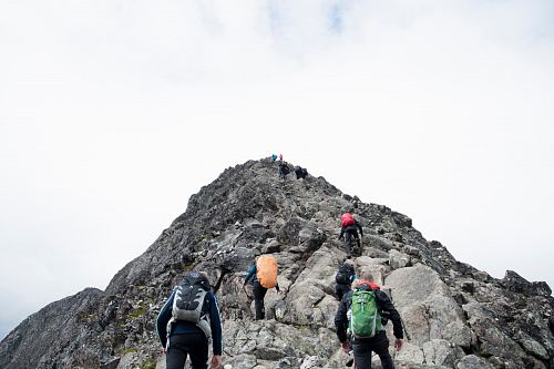 photo climbers hiking through mountain peak during daytime free for commercial use images
