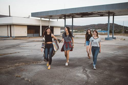 photo four girls walking near warehouse during daytime free for commercial use images