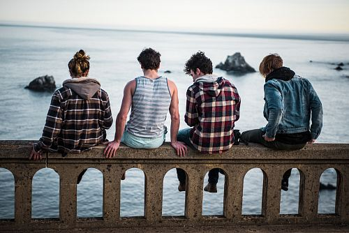 free for commercial use four person sitting on bench in front of body of water images