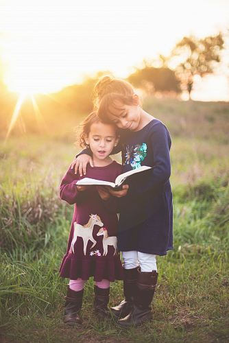 photo girl's left hand wrap around toddler while reading book during golden hour free for commercial use images