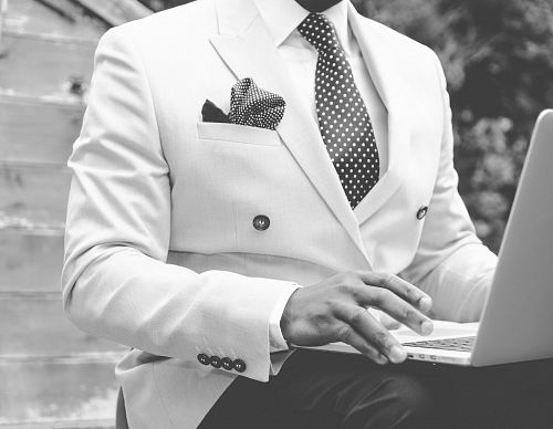 grayscale photo of man wearing suit jacket using laptop