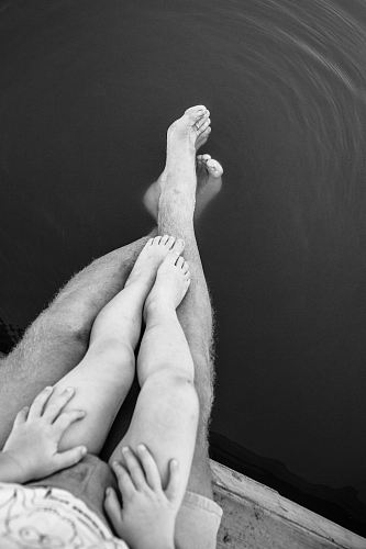 photo grayscale photo of person's feet on body of water free for commercial use images