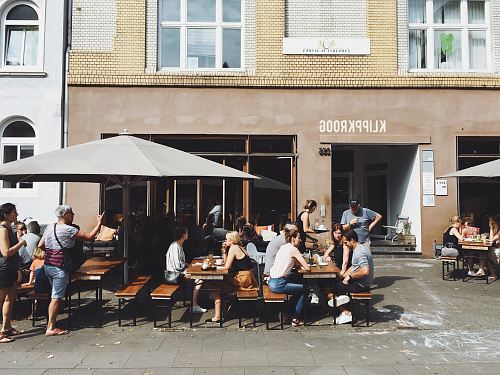 photo group of people sitting on benches with tables beside Klippkroog store front at daytime free for commercial use images