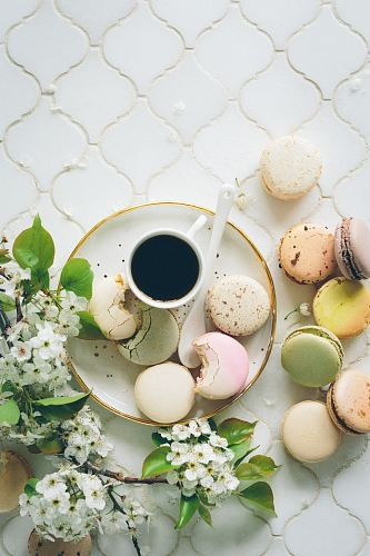photo macarons beside teacup and ladle on round white ceramic plate free for commercial use images