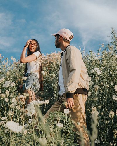 photo man and woman climbing white wild carrot flower fields free for commercial use images