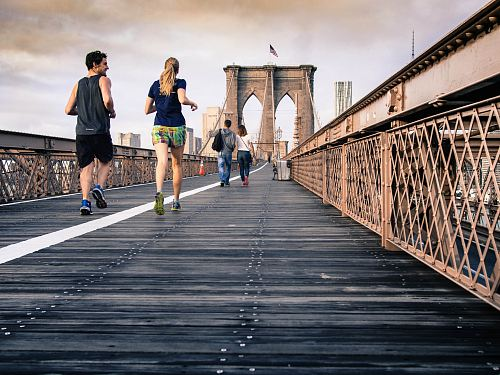 photo man and woman in black tops jogging at bridge under clear skies free for commercial use images