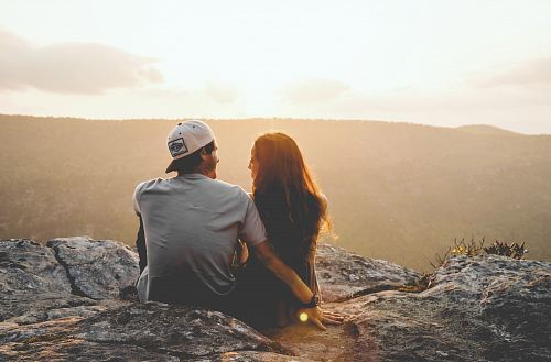 photo man and woman sitting on rock during daytime free for commercial use images