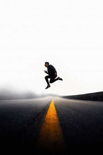 photo man jumping above gray and yellow concrete road at daytime free for commercial use images
