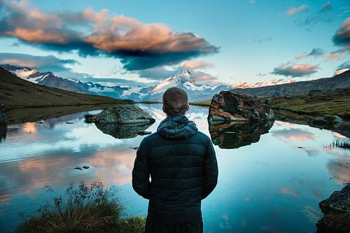 photo man standing in front view of lake surrounded with mountains free for commercial use images