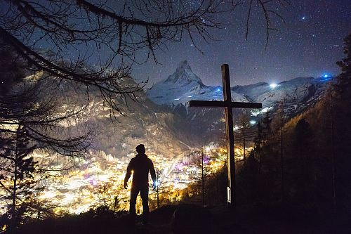 photo man standing near cross during night free for commercial use images
