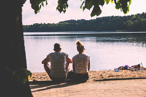 photo men and woman sitting on pavement facing body of water free for commercial use images
