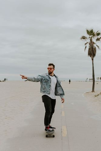 photo men's washed denim jacket riding a skateboard free for commercial use images