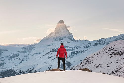 photo person in red hoodie standing on snowy mountain during daytime free for commercial use images