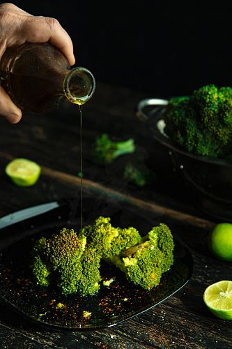 person pouring cola on broccoli