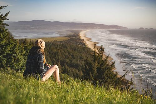 photo person sitting on hill near ocean during daytime free for commercial use images