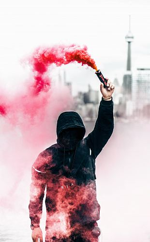 photo person wearing black and red hoodie holding smoke bomb free for commercial use images