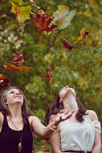 photo photo of two women throwing leaves during daytime free for commercial use images