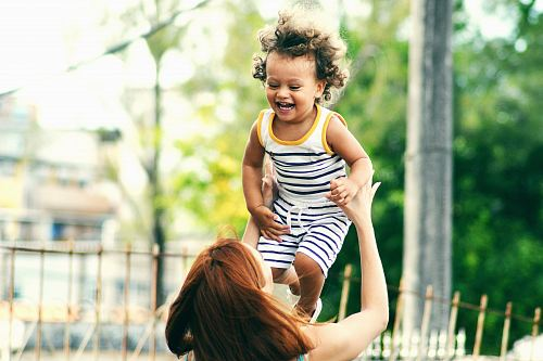 photo selective focus photo of woman lifting child during daytime free for commercial use images