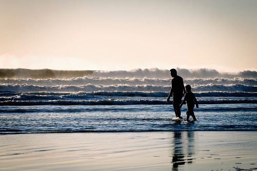 photo silhouette of a man and a boy on the seashore free for commercial use images