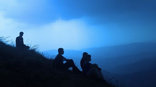 photo silhouette of men sitting on mountain free for commercial use images