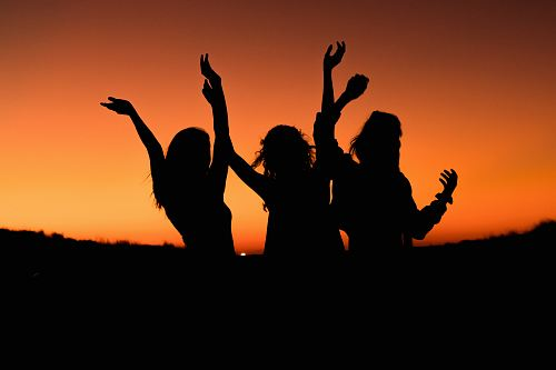 photo silhouette of three woman with hands on the air while dancing during sunset free for commercial use images