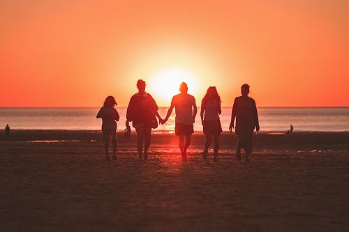 photo silhouette photo of five person walking on seashore during golden hour free for commercial use images
