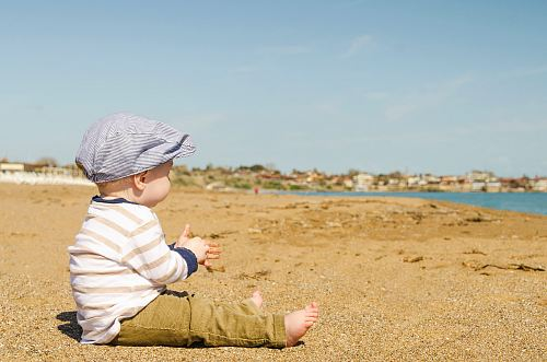 photo sitting toddler on seashore at daytime free for commercial use images