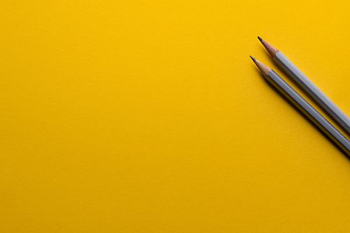 photo two gray pencils on yellow surface free for commercial use images