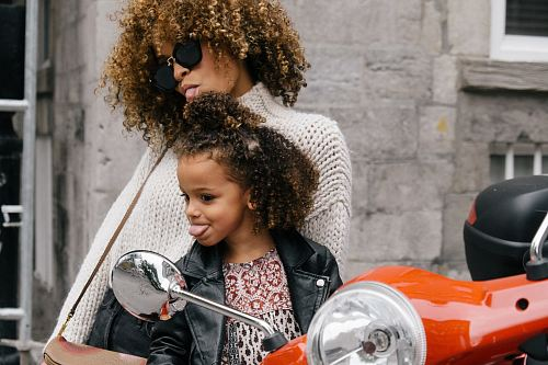 photo woman and girl showing their tongues beside motorcycle free for commercial use images