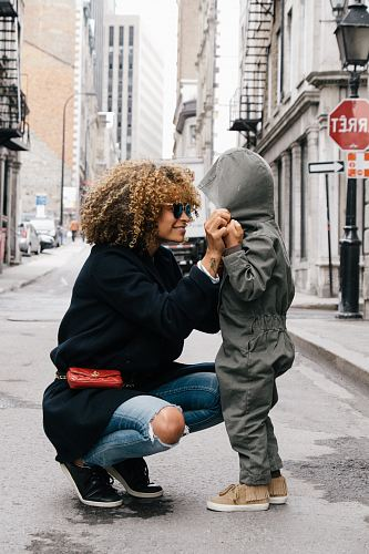 photo woman holding kid at the street free for commercial use images