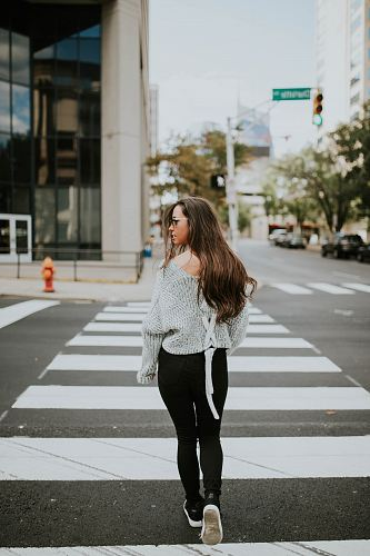 photo woman looking towards her right while walking along pedestrian lane during daytime free for commercial use images