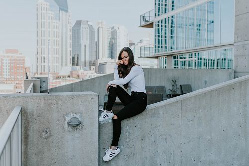 photo woman sitting on concrete building free for commercial use images