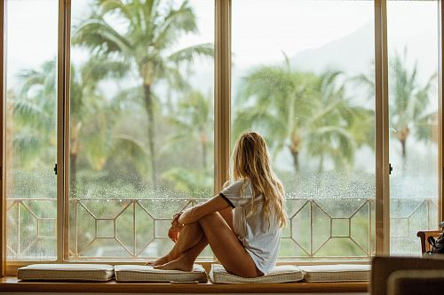 photo woman sitting on white cushion near glass window free for commercial use images