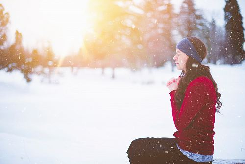 photo woman sitting with closed eyes surrounded by snow free for commercial use images
