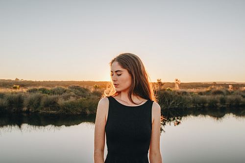 woman standing near pond