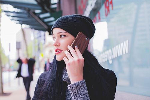 photo woman wearing beanie with smartphone on ear free for commercial use images