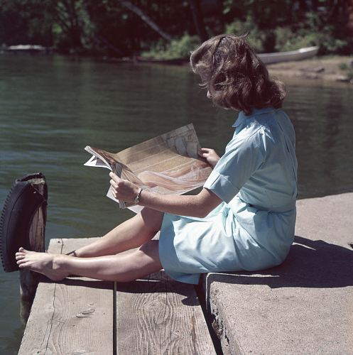 photo woman wearing blue dress reading magazine near body of water during daytime free for commercial use images