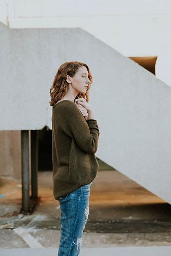 woman wearing brown sweatshirt and whiskered distressed blue jeans