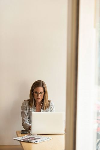 photo woman wearing grey striped dress shirt sitting down near brown wooden table in front of white laptop computer free for commercial use images