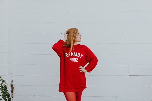 photo woman wearing red long-sleeved shirt standing near white painted wall free for commercial use images