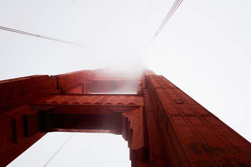 fog worm eye view photography of brown building golden gate bridge
