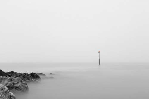 grey photo of pillar bouy on body of water rocks