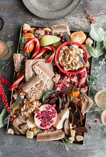 holiday variety of sliced fruits, cookies, and chocolates on gray steel tray food