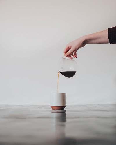 minimal person pouring coffee in white mug minimalist