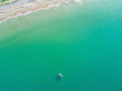 ocean aerial photography of white boat on green ocean near seashore sea