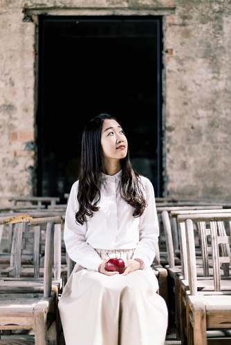 woman woman in white button-up dress shirt and white pants holding apple sitting on chair apple