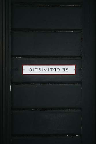 sign black wooden door with be optimistic text overlay words